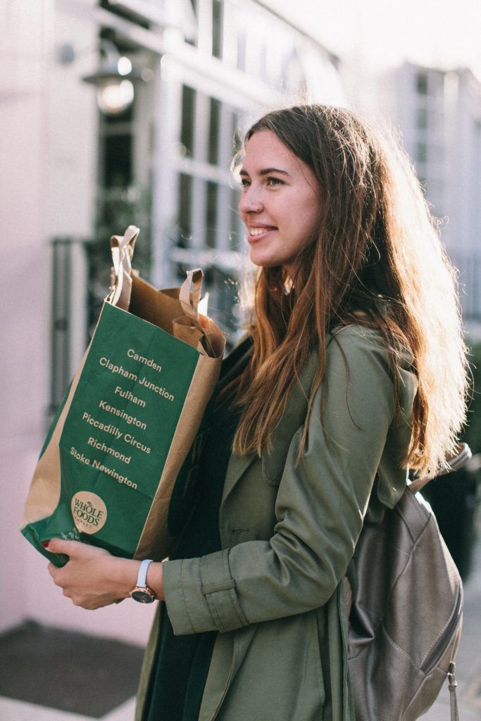 A girl smiling while carrying a paper bag.