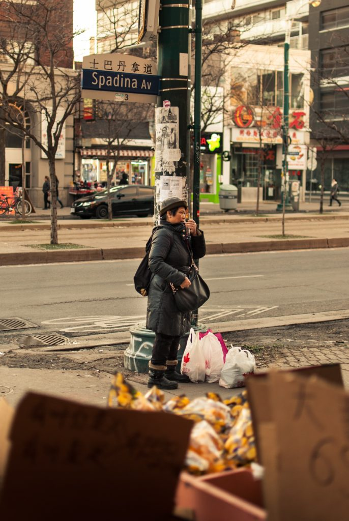 A woman standing with plastic bags full of items on the ground next to her.