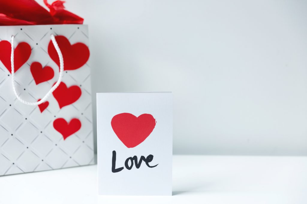 A white personalized bag, designed with red hearts placed on the left side and a white card with a red heart and Love word in the center.